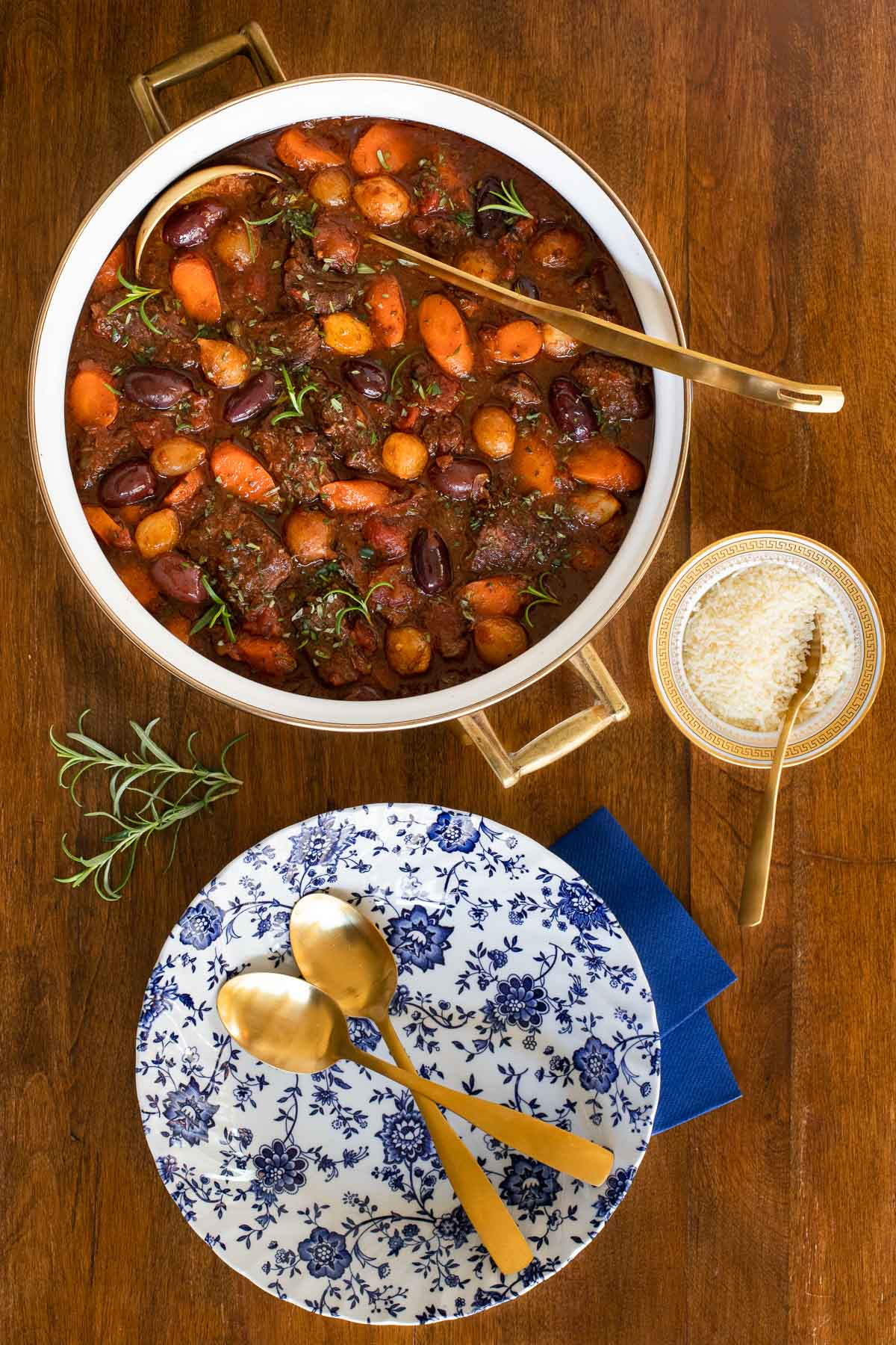 Overhead vertical photo of a pot of Slow Braised Italian Beef Stew on a wood table.