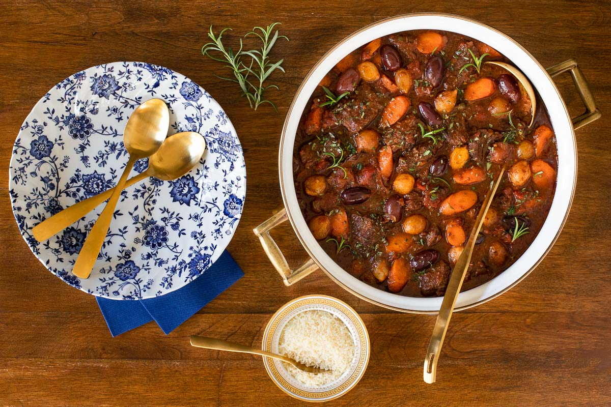Horizontal overhead photo of a pot of Slow Braised Italian Beef Stew on a wood table.