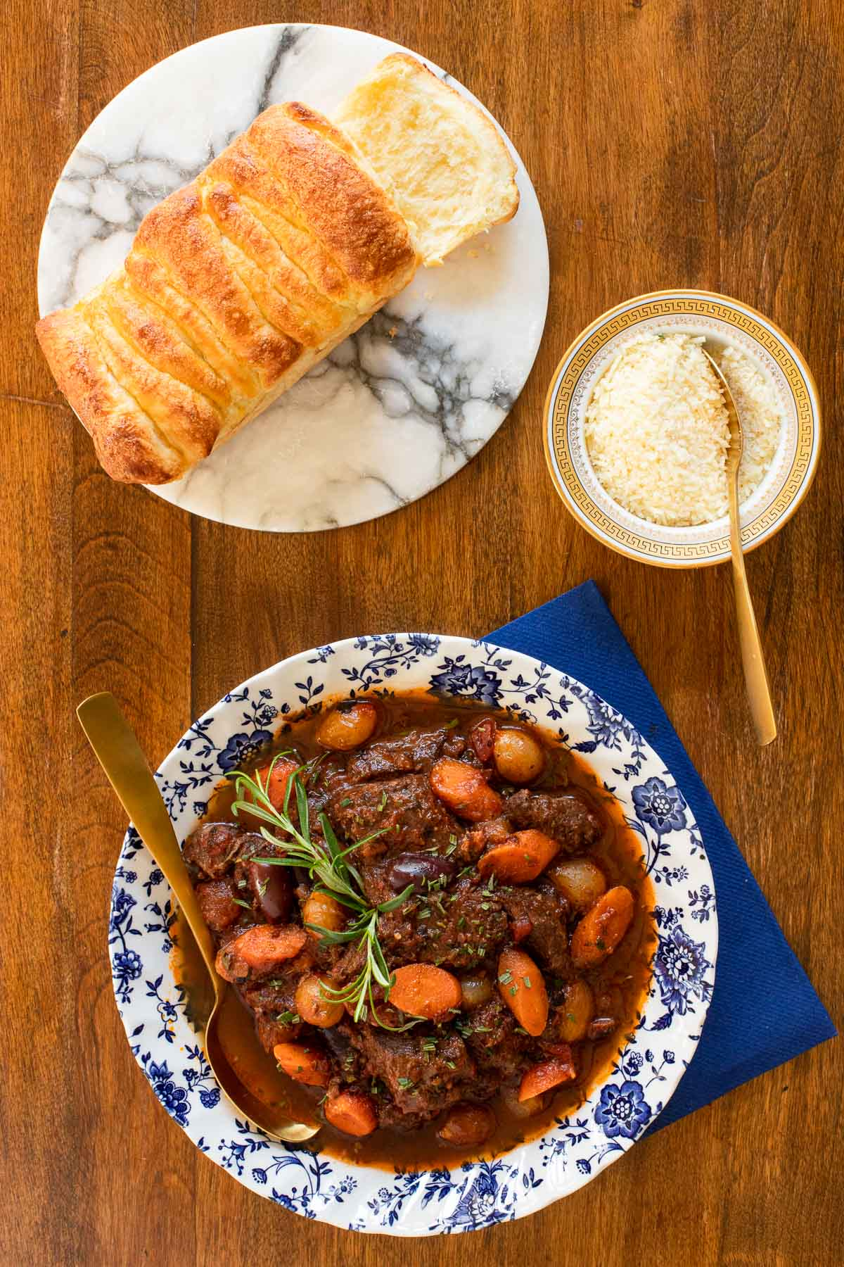 Vertical overhead photo of a blue and white patterned bowl of Slow Braised Italian Beef Stew with a loaf of crusty homemade bread and a dish of shredded cheese nearby.