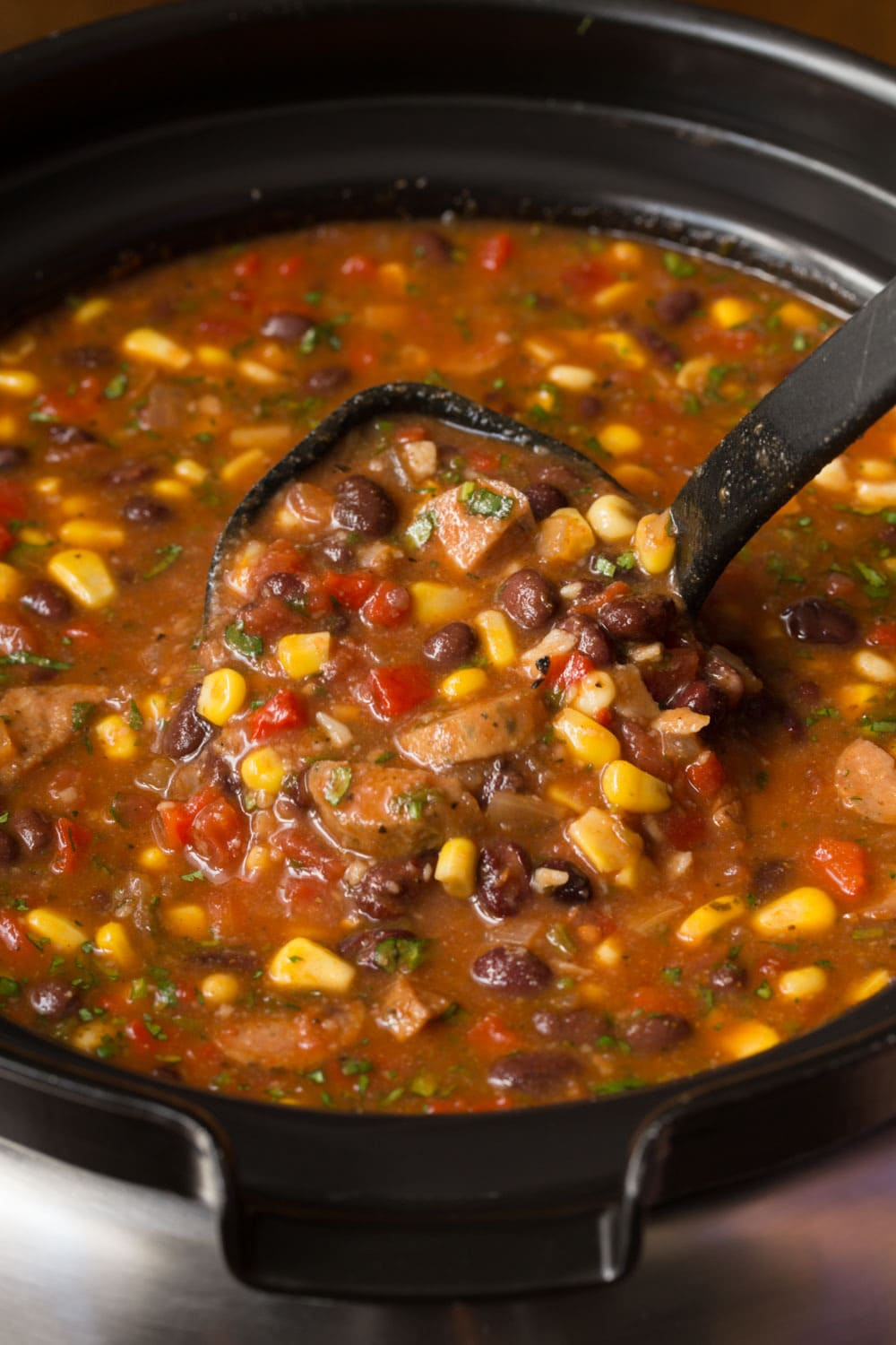 A photo of a pot of Slow Cooker Black Bean and Chicken Sausage Tortilla Soup, one of The Cafe Sucre Farine's Soup Recipes. A black ladle is lifting a portion of the soup.