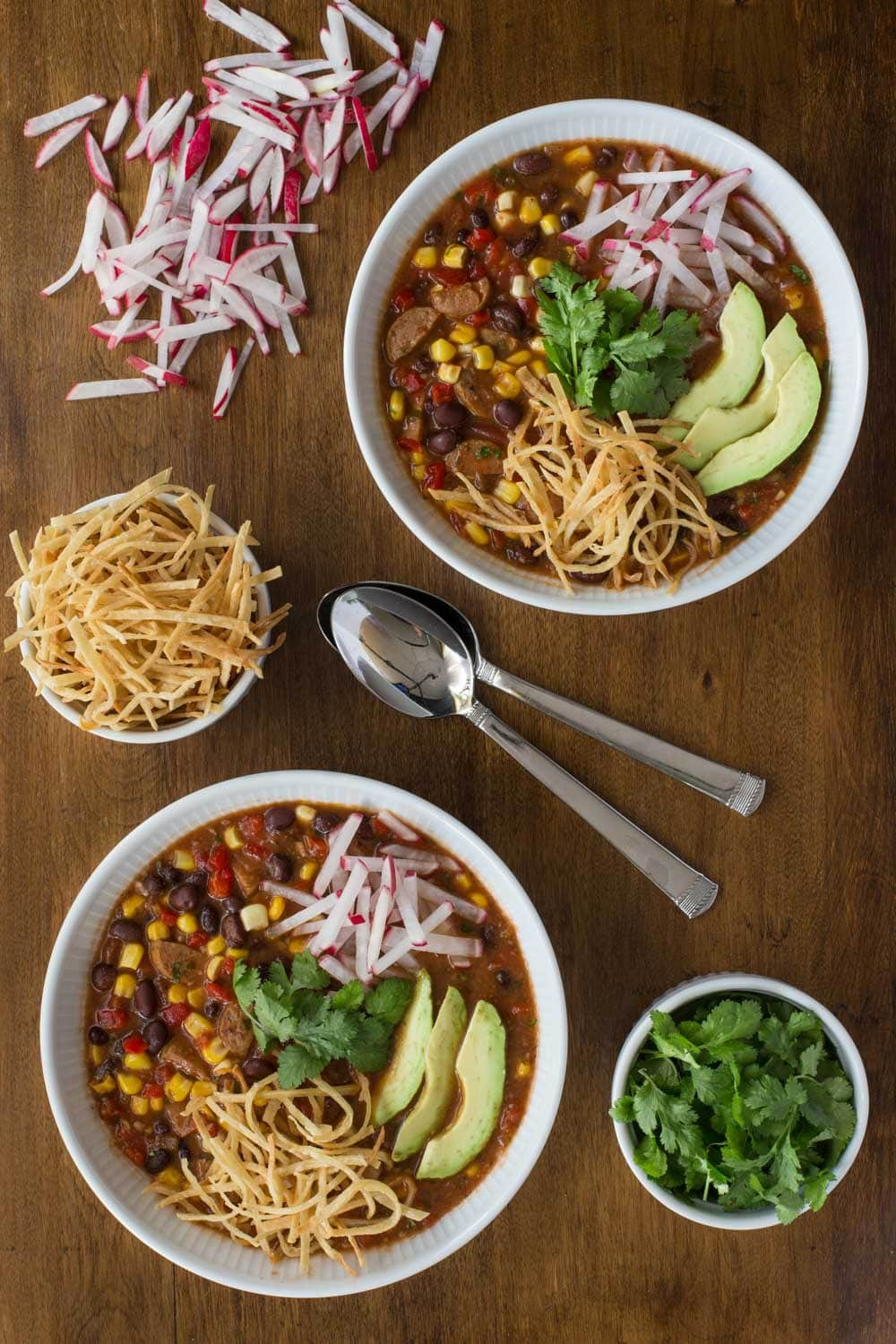 Overhead vertical photo of Slow Cooker Black Bean and Chicken Sausage Tortilla Soup in white serving bowls surrounded by bowls of toppings.