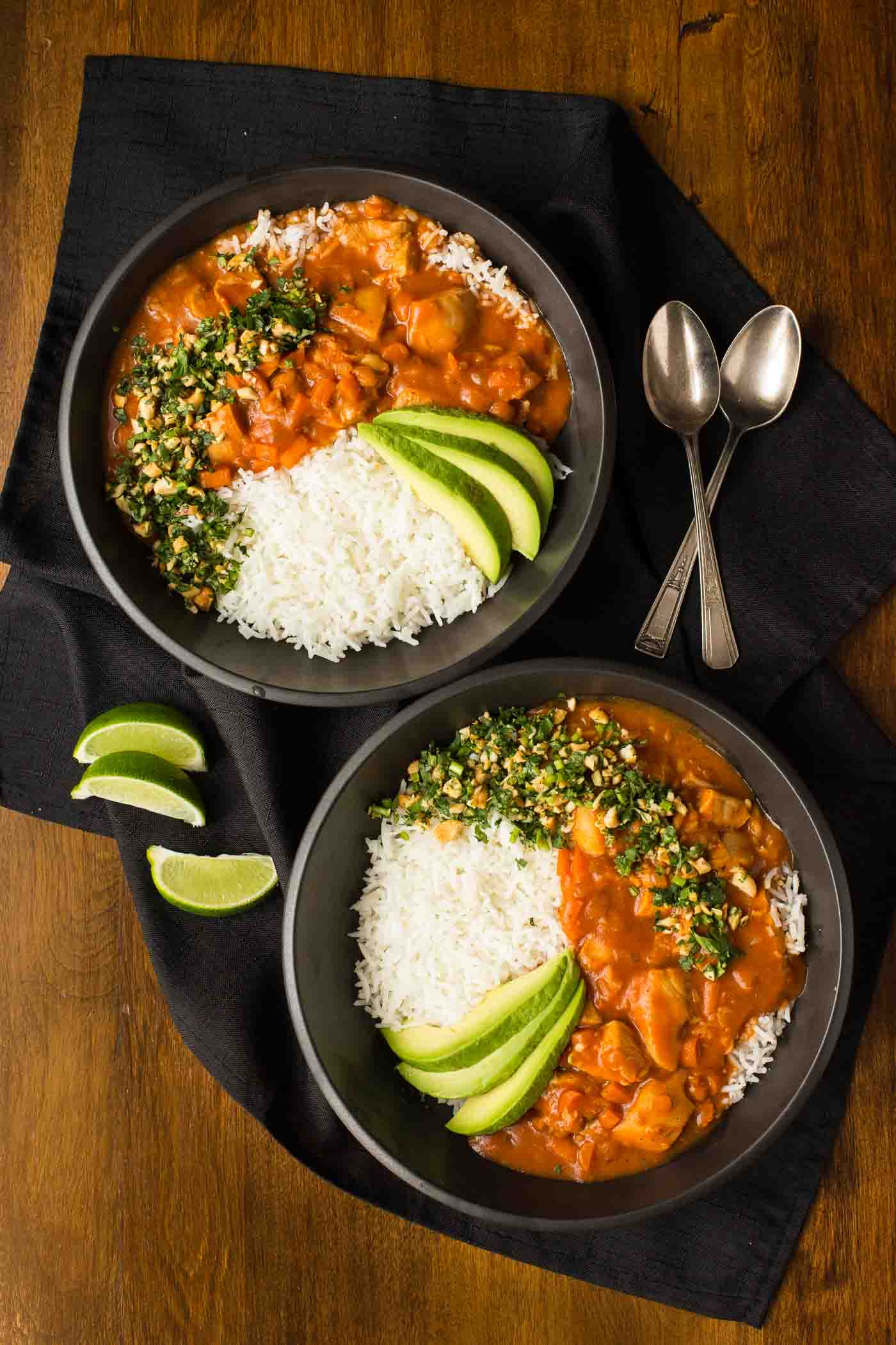 Overhead photo of two black bowls of Slow Cooker Indian Butter Chicken with rice, cilantro cashew garnish and sliced avocados.