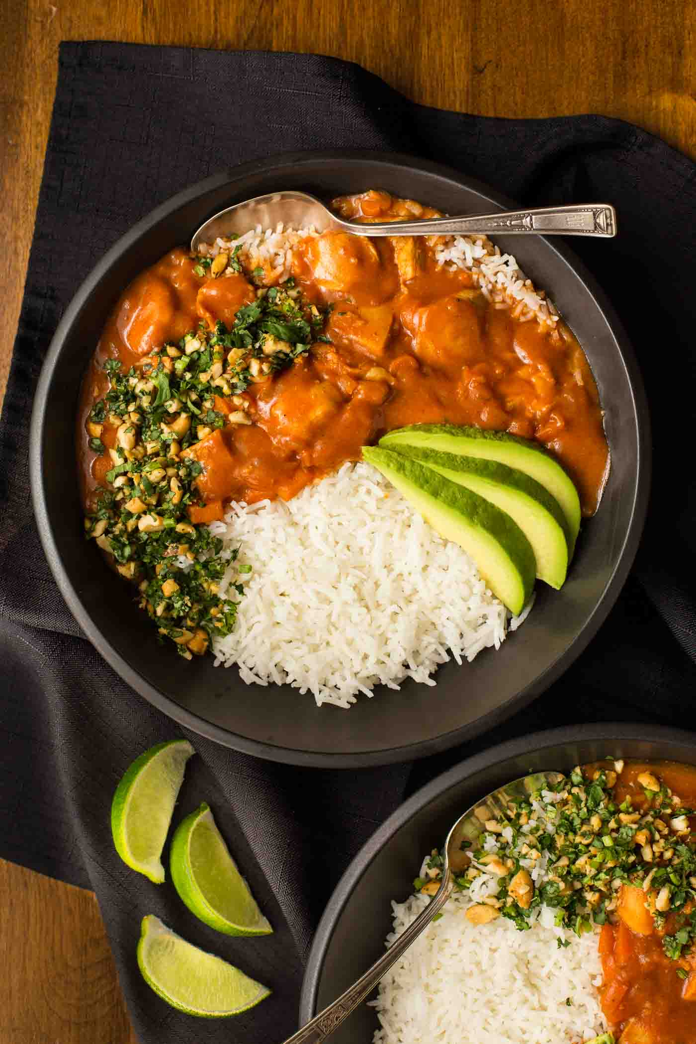 Overhead photo of two black bowls of Slow Cooker Indian Butter Chicken with rice, sliced avocados and cilantro cashew garnish.