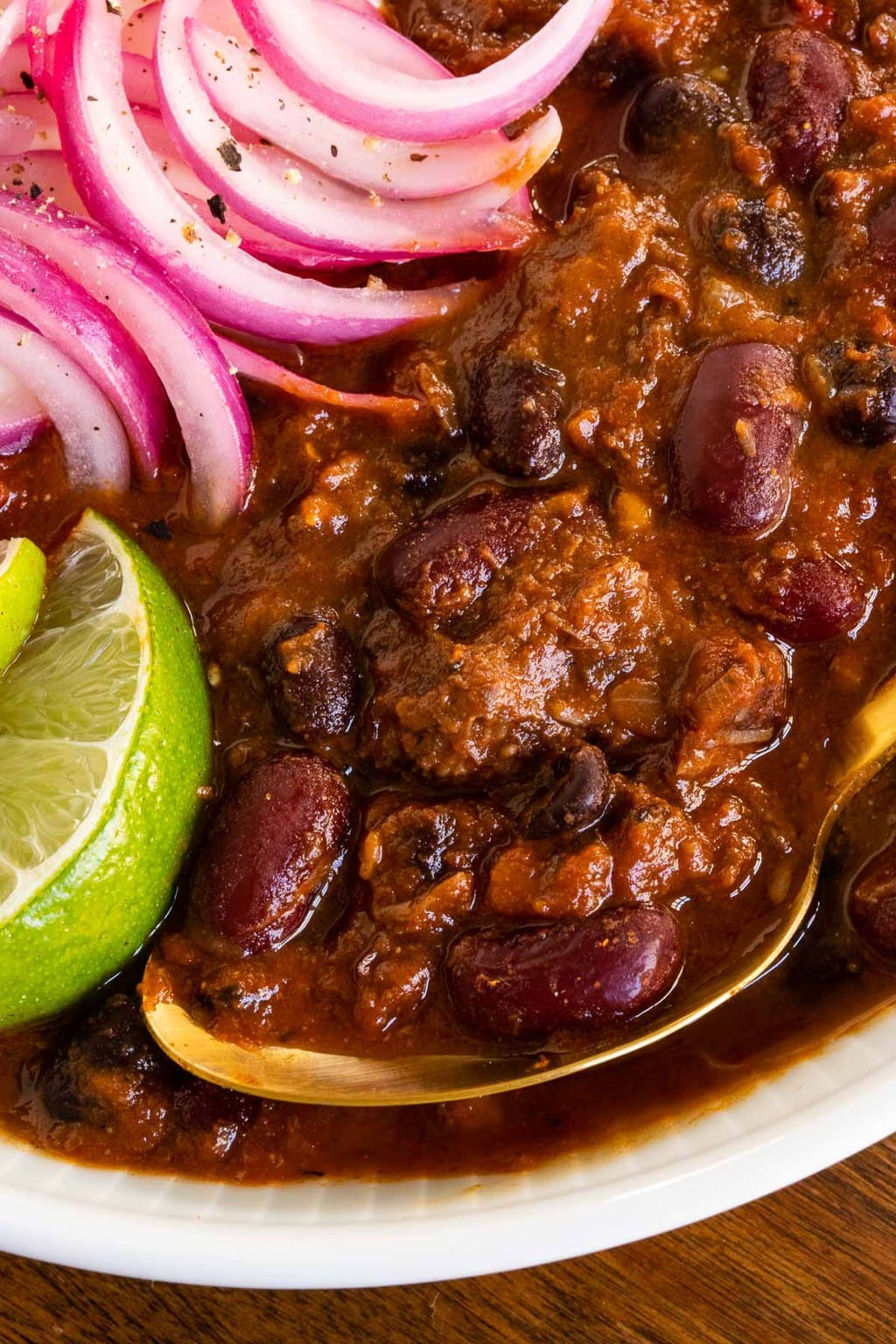 Ultra closeup photo of Slow Roasted Short Rib Chili with pickled onions and lime wedges as garnishes.