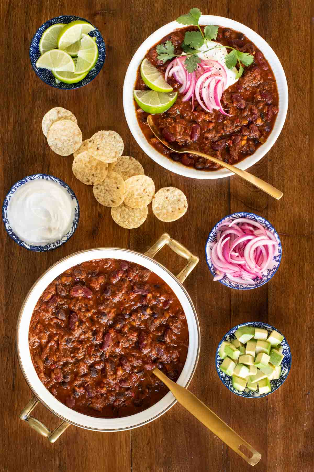 Overhead photo of a pot and an individual serving of Slow Roasted Short Rib Chili with bowls of diced avocados, lime wedges, tortilla chips, sour cream and pickled onions for garnish.