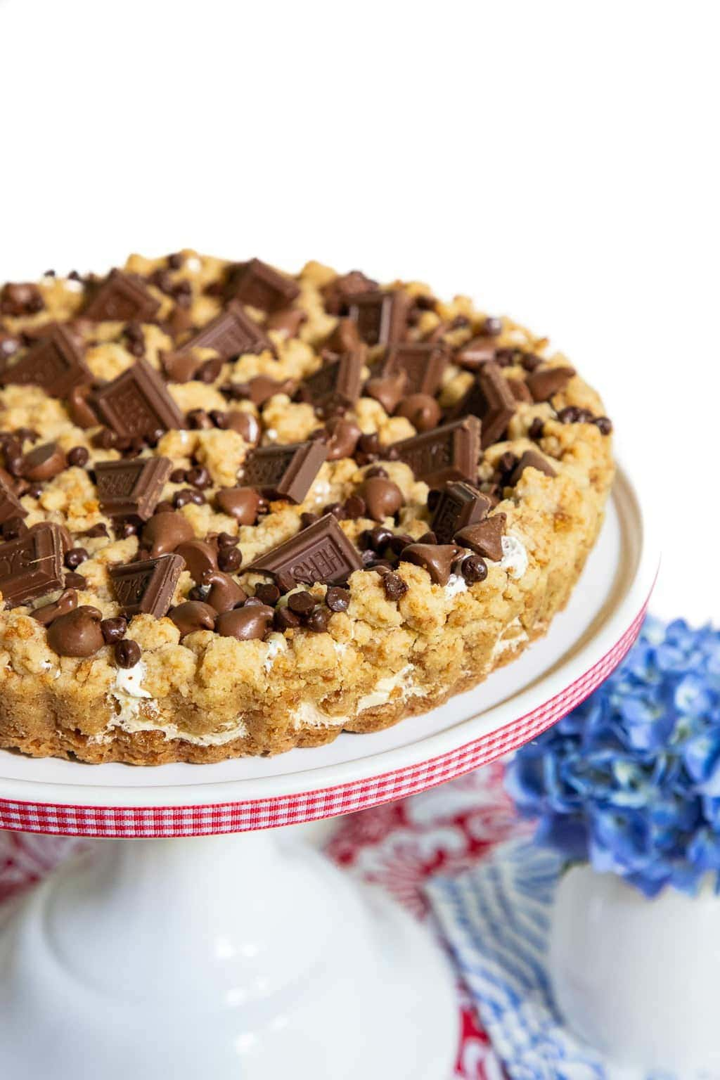Vertical photo of a S'mores Shortbread Tart on a white pedestal dessert stand festooned with white and red ribbon.