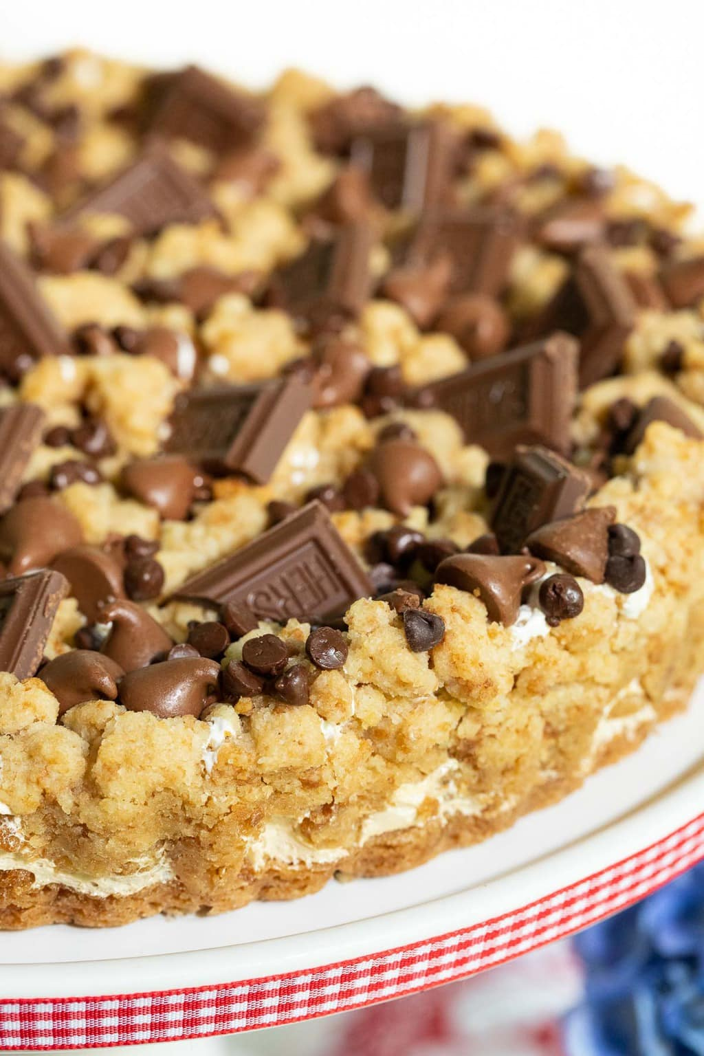 Vertical side closeup photo of a Easy S'Mores Shortbread Tart on a white pedestal plate with red and white checked ribbon around the edge.