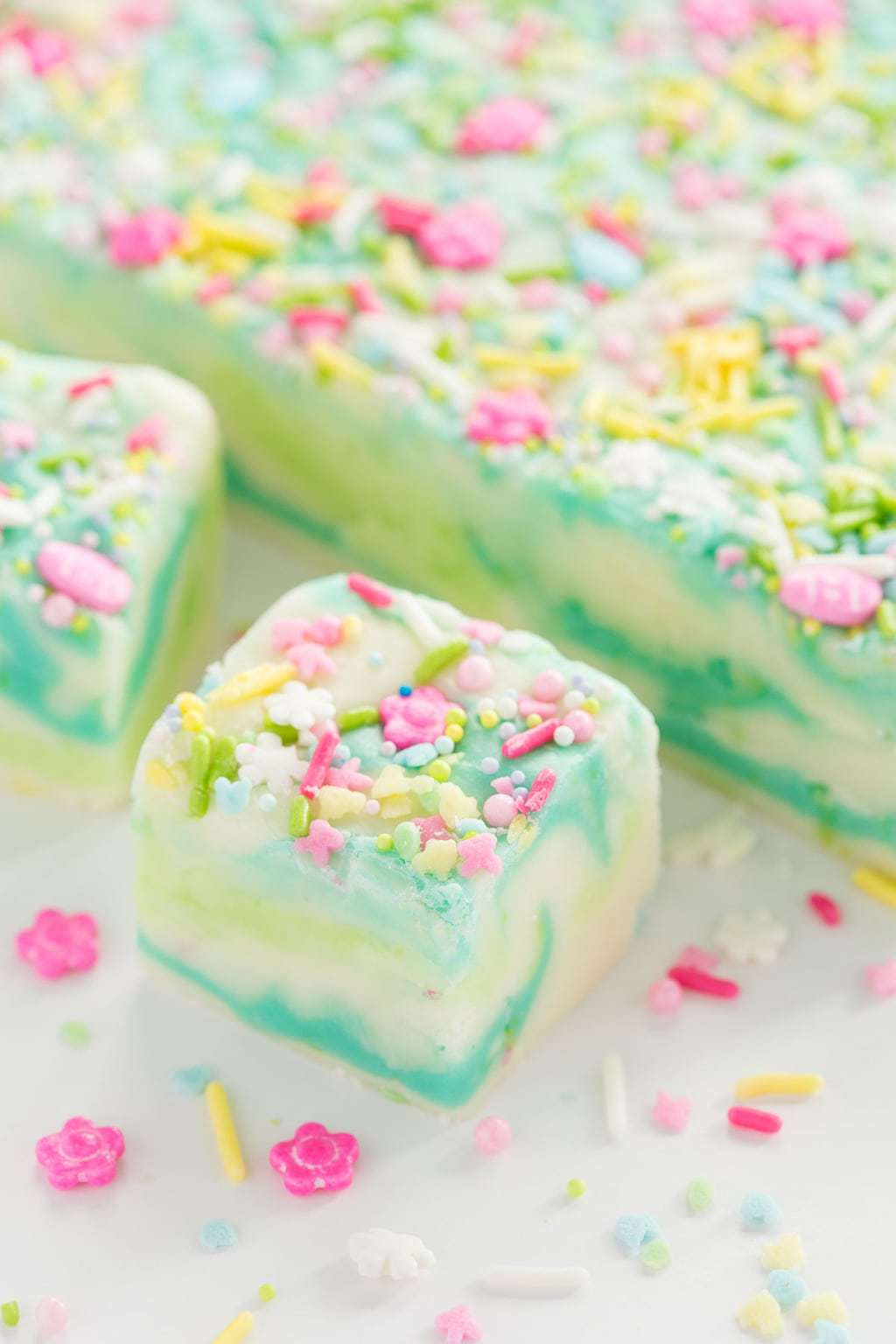 Photo of a slab of Spring Fantasy Fudge with individually cut pieces in the foreground with spring colored sprinkles.