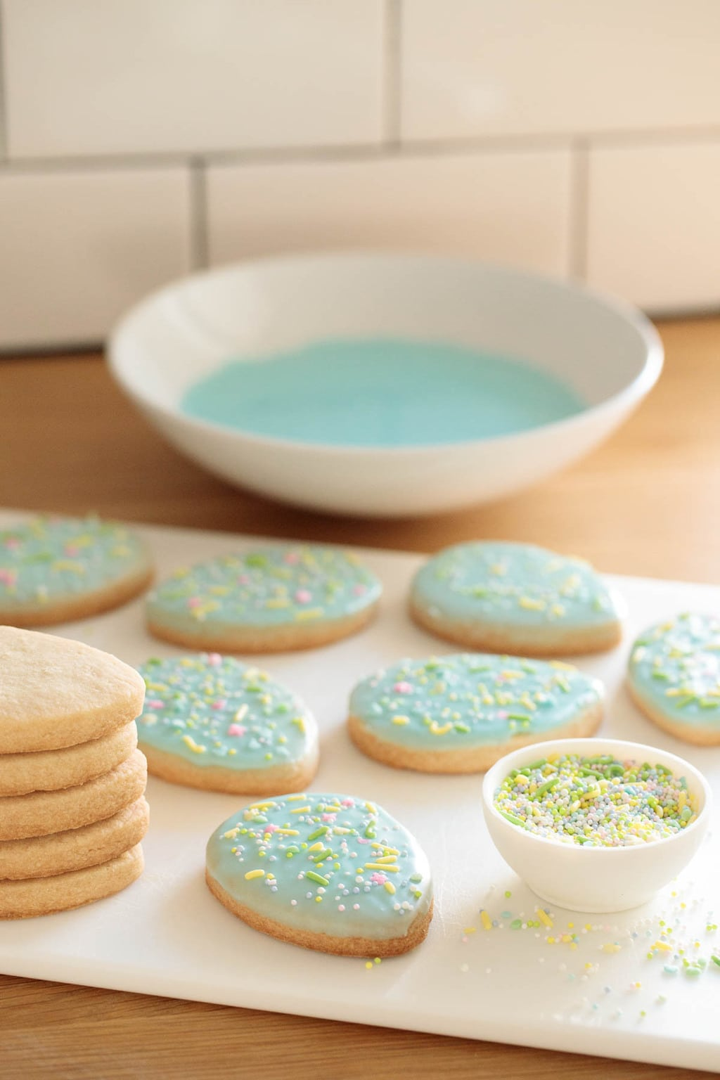 Photo of a white cutting board filled with Spring Shortbread Cookies with a bowl of frosting in the background and a dish of pastel sprinkles in the foreground.