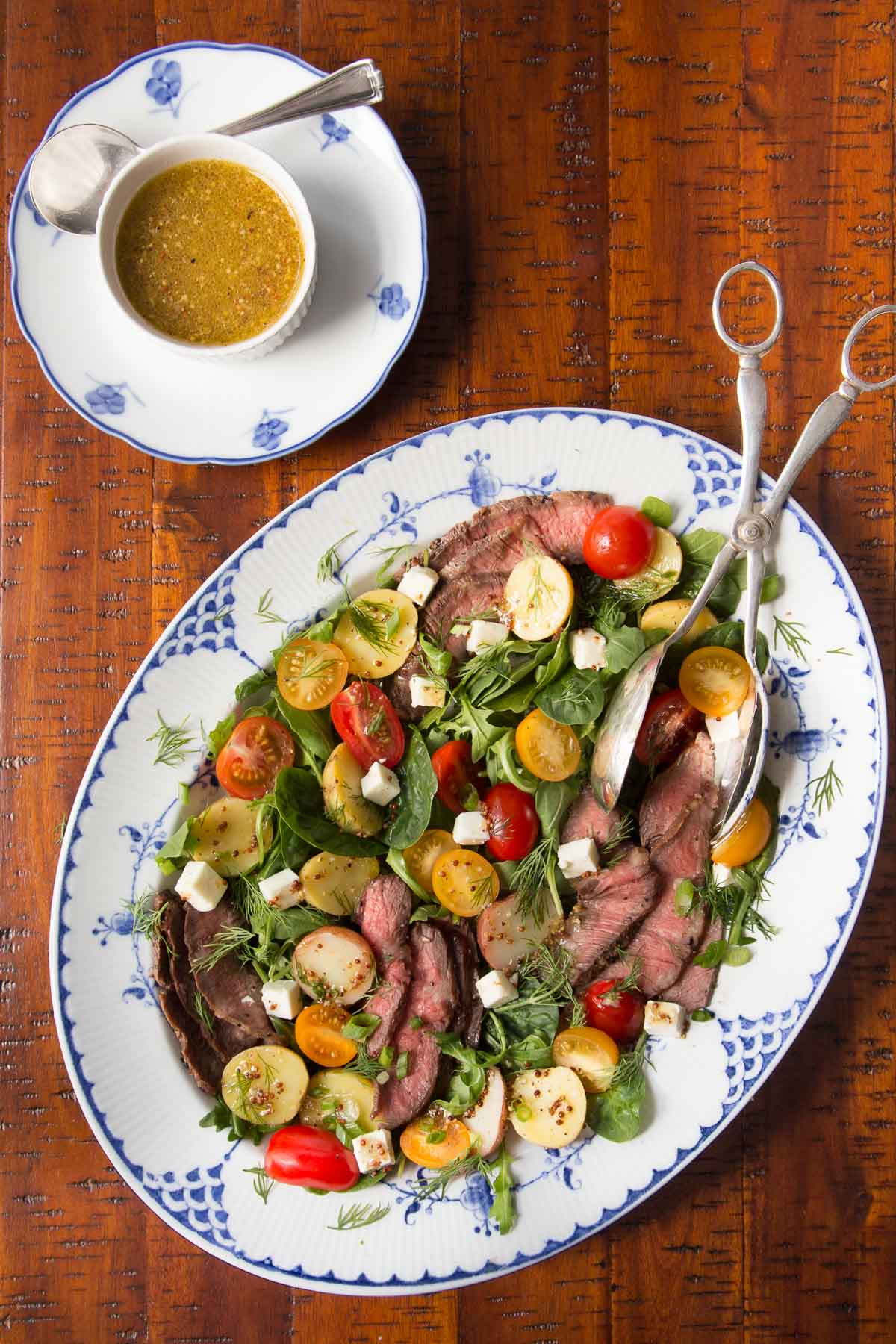 Overhead photo of a blue and white patterned platter filled with a Steak and Potato Arugula Salad on a distressed wood table. A cup of salad dressing is next to the platter.