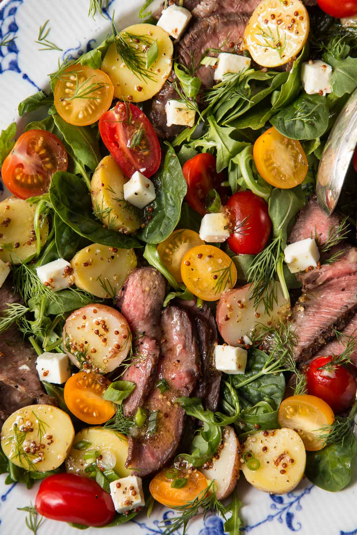 Closeup of a platter of Steak and Potato Arugula Salad on a blue and white platter.