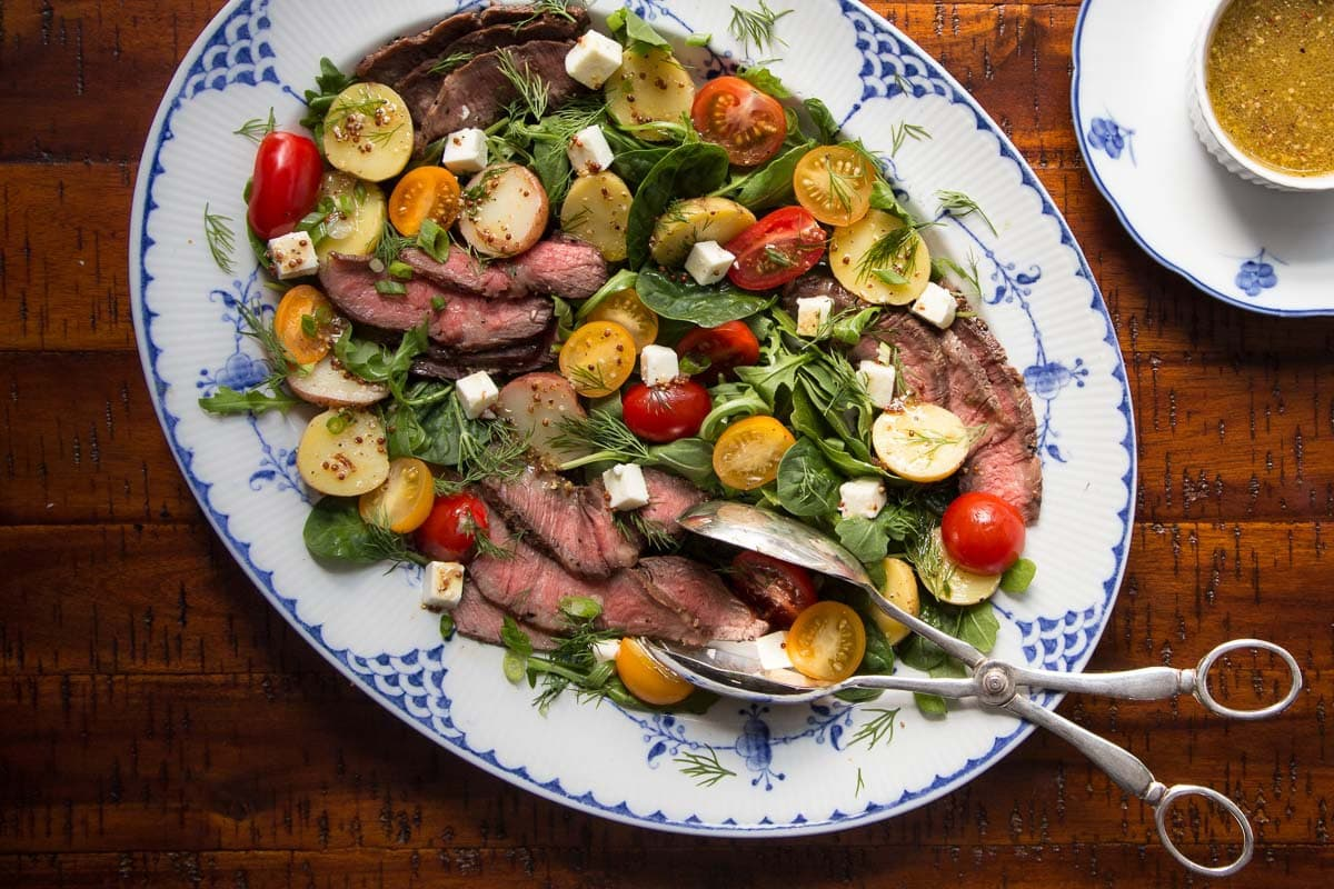 Overhead photo of a Steak and Potato Arugula Salad on a blue and white patterned serving platter on a distressed wood table.