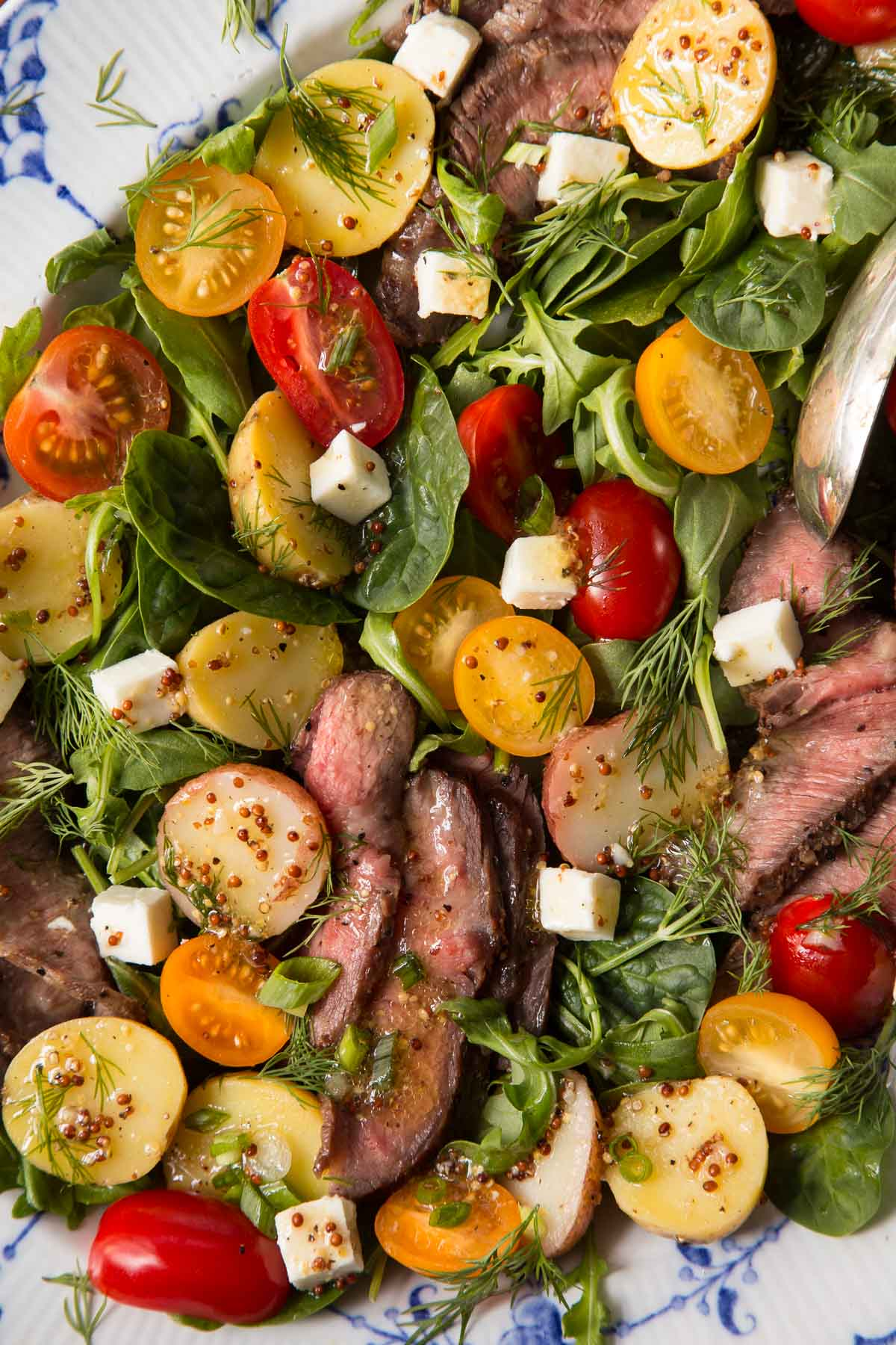 Closeup of a platter of Steak and Potato Arugula Salad.