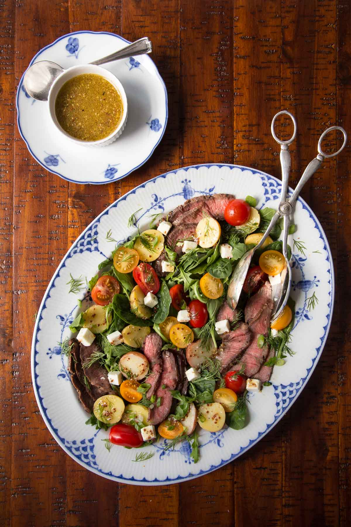 Overhead photo of a serving dish of Steak and Potato Arugula Salad with a cup of champagne vinaigrette dressing.
