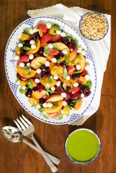 Overhead picture of Stone Fruit Tomato Salad on a white and blue platter
