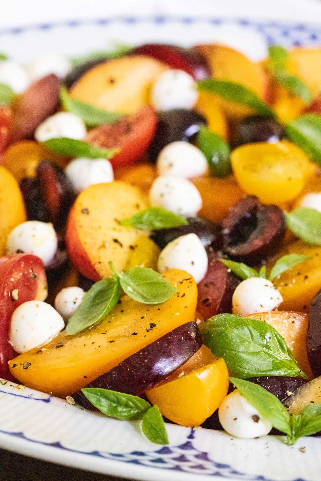 Closeup side photo of a blue and white presentation platter filled with Stone Fruit Tomato Caprese Salad.