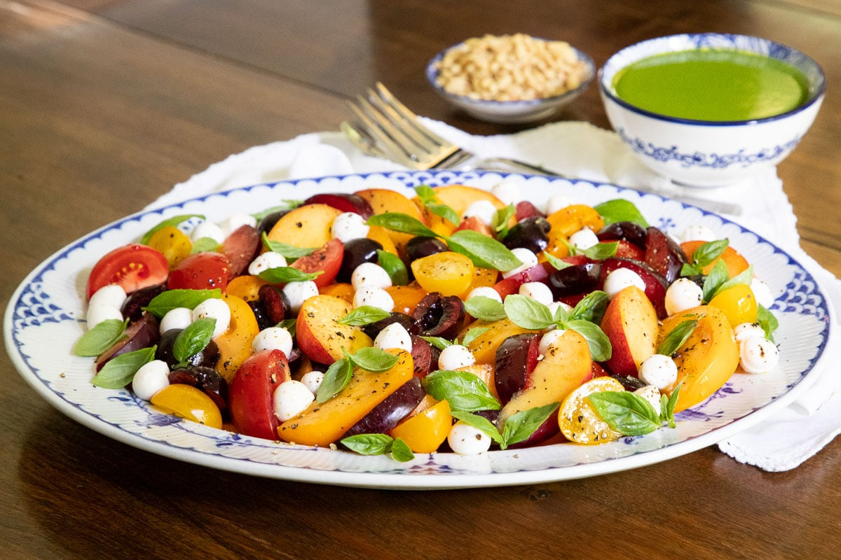 Horizontal photo of a Stonefruit Caprese Salad on a blue and white patterned serving platter.