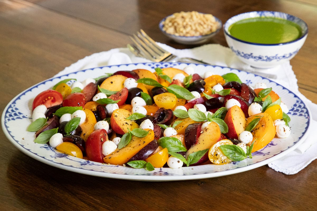 Horizontal photo of a serving platter of Stone Fruit Tomato Caprese Salad on a wood table.