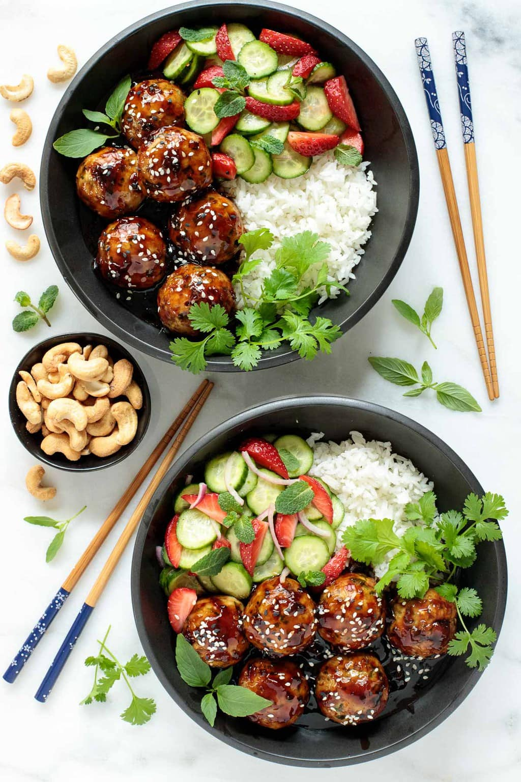 Overhead photo of two black bowls filled with Strawberry Balsamic Glazed Chicken Meatballs with fresh cucumbers, strawberries and herbs with a bed of rice on one side.