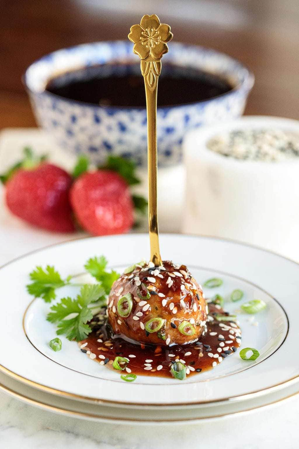 Closeup photo of a white and gold-rimmed appetizer plate with a Strawberry Balsamic Glazed Chicken Meatball in the center garnished with cilantro and green onions.