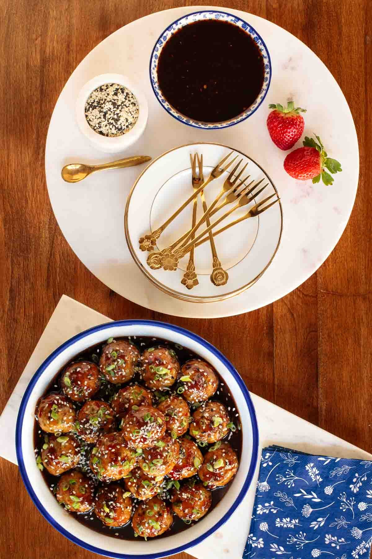 Overhead vertical photo of Strawberry Balsamic Glazed Chicken Meatballs with accessories for serving them as appetizers.