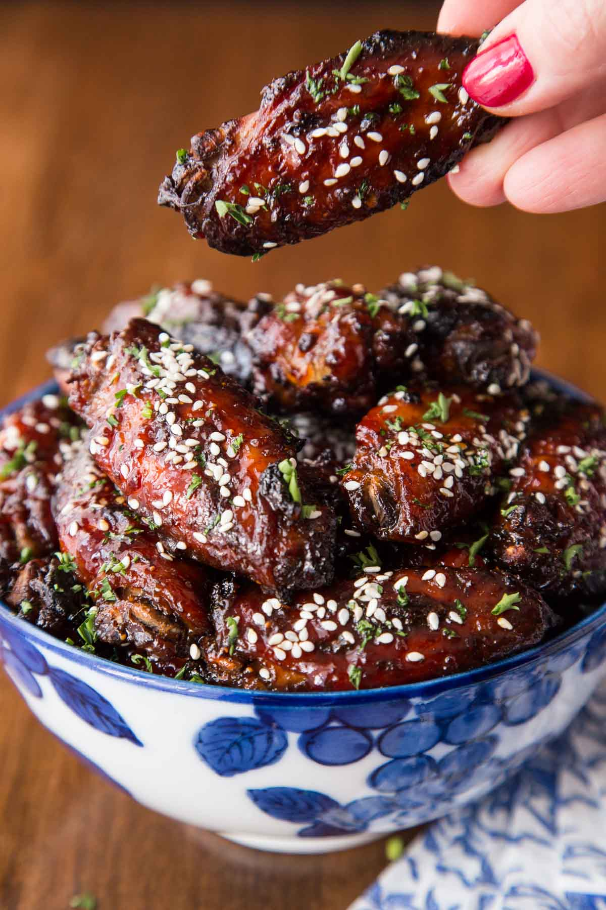 Vertical photo of strawberry balsamic wings garnished with sesame seeds in a blue and white bowl. A person's is holding one above the dish.