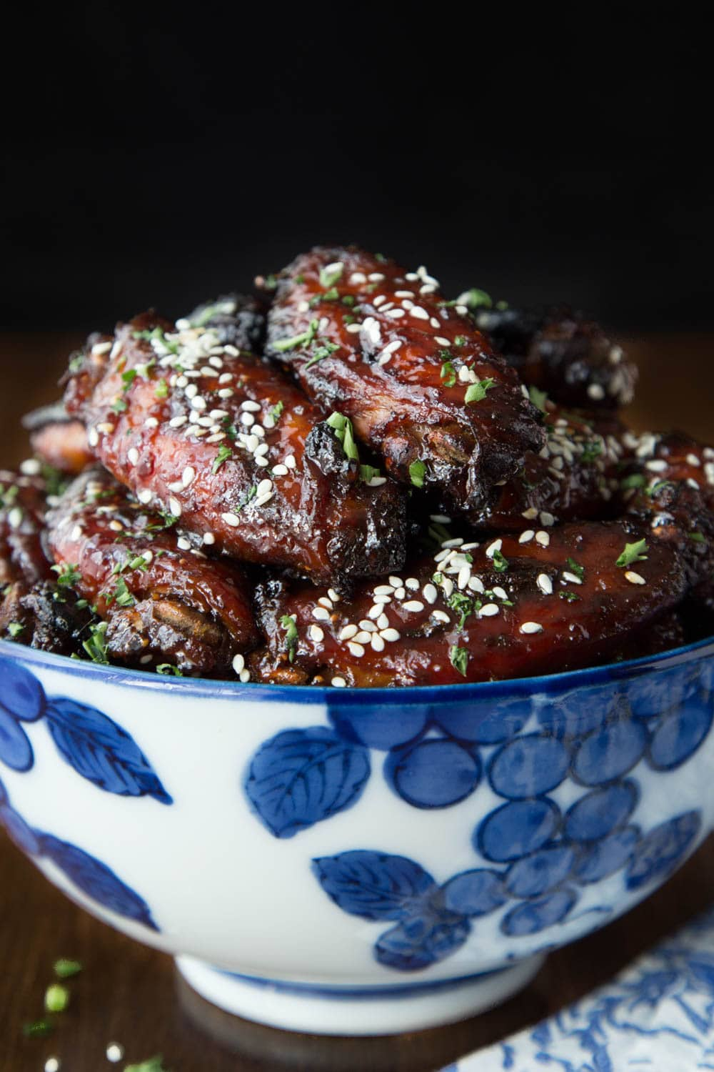 Photo of a blue and white patterned bowl filled with Strawberry Balsamic Glazed Wings.