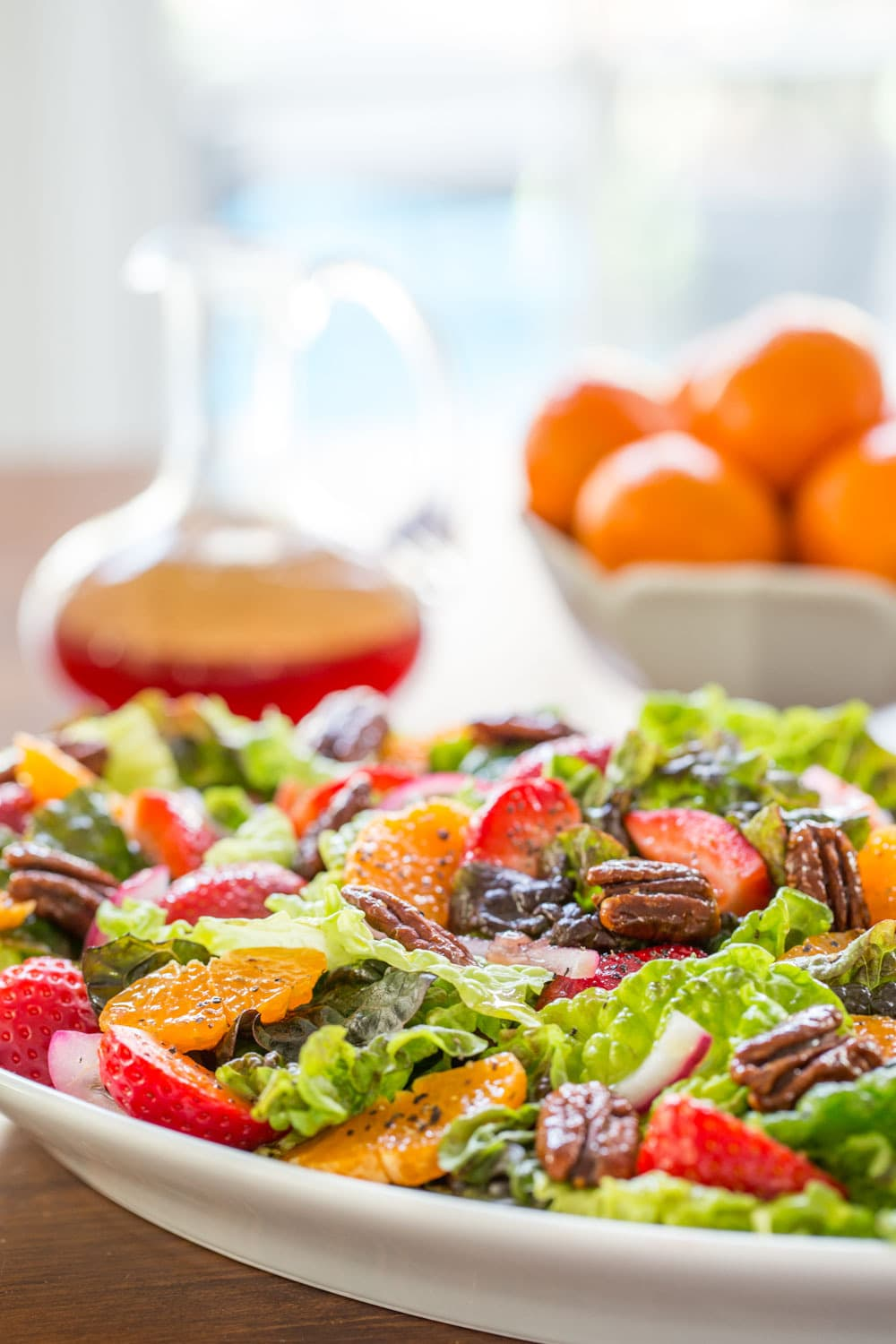 Vertical picture of Strawberry Clementine Salad on a white platter with dressing in the background