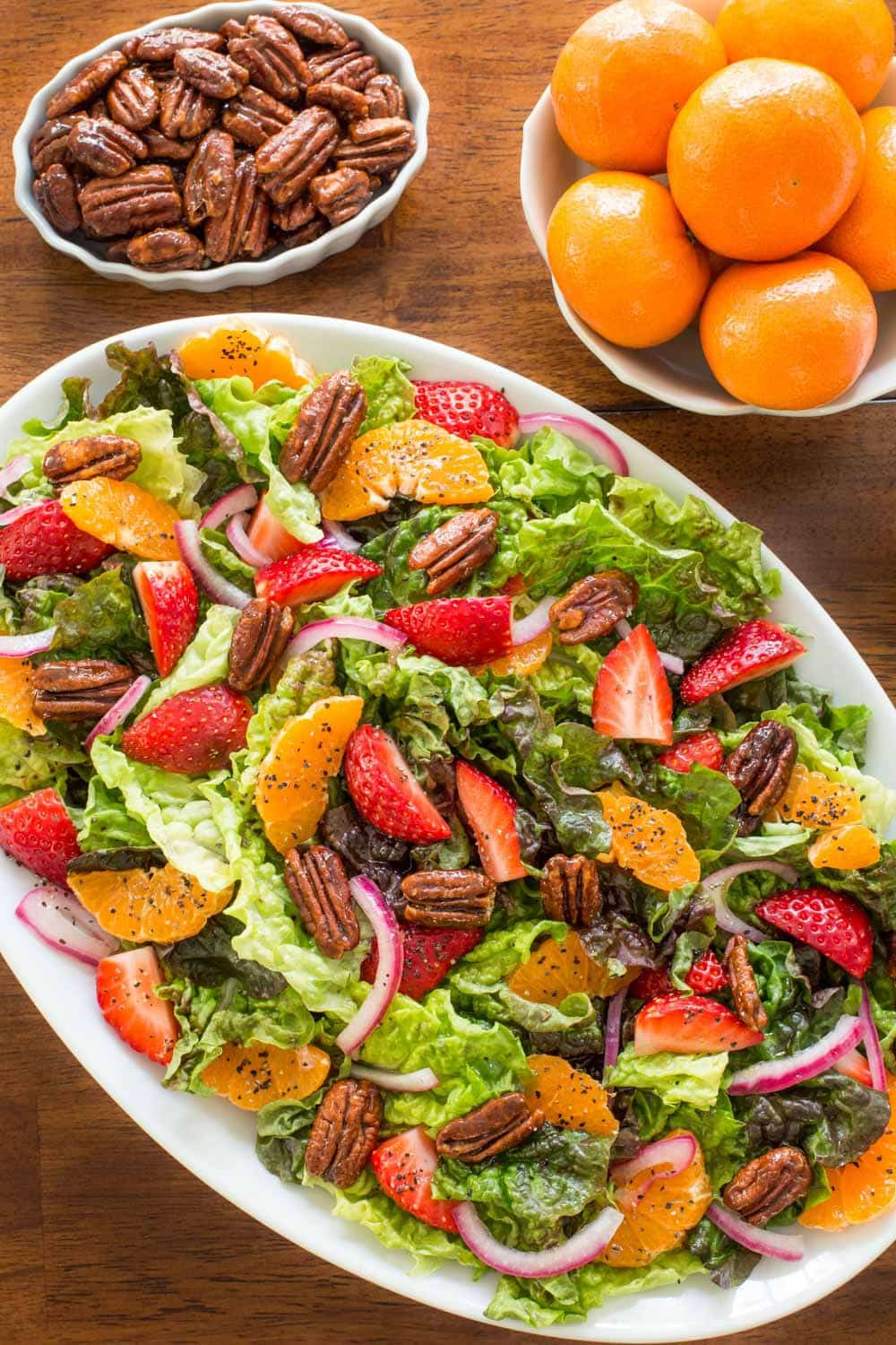 Overhead photo of a Strawberry Clementine Salad with Red Wine Vinegar Dressing on a white platter with bowls of clementines and pecans.