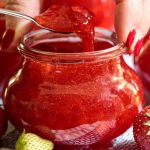 Vertical picture of strawberry freezer jam in a glass jar