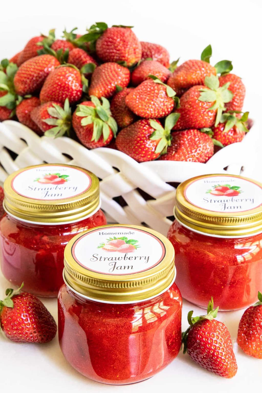 Vertical picture of strawberry jam in jars with a big basket of strawberries in the background