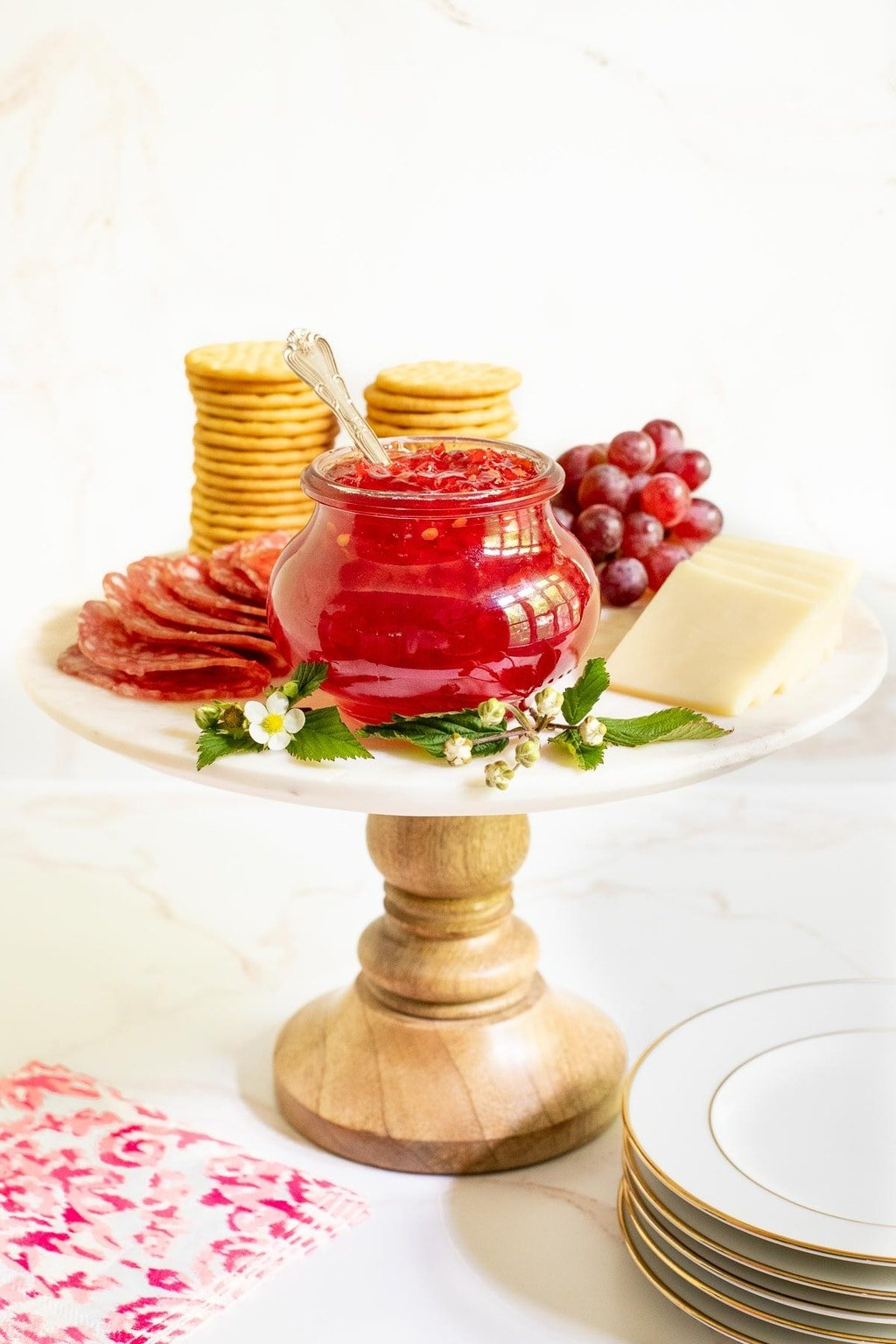 Vertical photo of a jar of Strawberry Habanero Pepper Jelly on a marble and wood pedestal stand surrounded by charcuterie items.