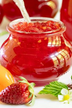 Horizontal closeup photo of a jar of Strawberry Habanero Pepper Jelly with additional jars in the background and a strawberry and a habanero pepper in the foreground.