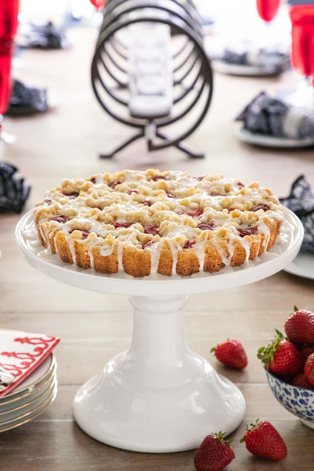 Vertical photo of Strawberry Jam Shortbread Tart on a white cake stand sitting on a dining room table.