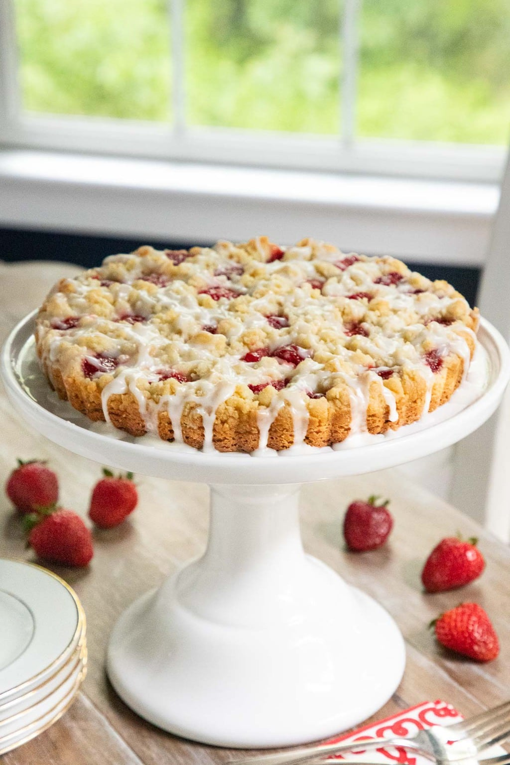 Vertical photo of a Strawberry Jam Shortbread Tart on a white pedestal cake stand.