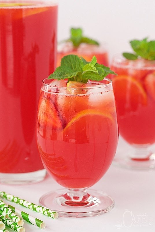 A horizontal photo of a glass of Strawberry Lemonade surrounded by glasses and a pitcher filled with the drink. Glasses are garnished with a sprig of mint.
