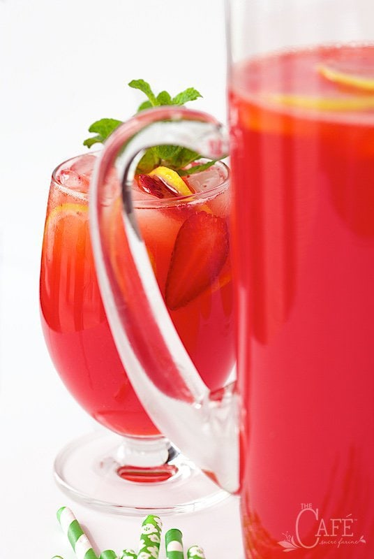 A glass of Strawberry Lemonade garnished with mint peeking out from behind the handle of a pitcher of the drink.