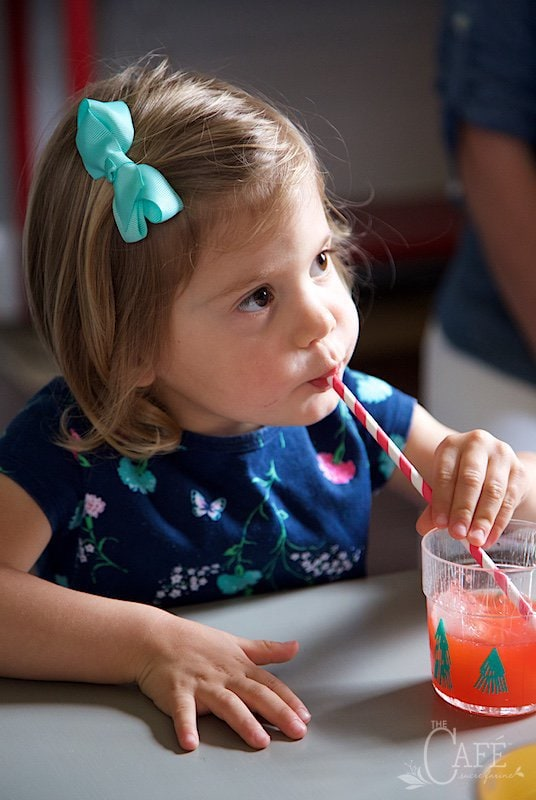 Horizontal photo of a child dressed up and sipping on a festive straw in a glass of Strawberry Lemonade.
