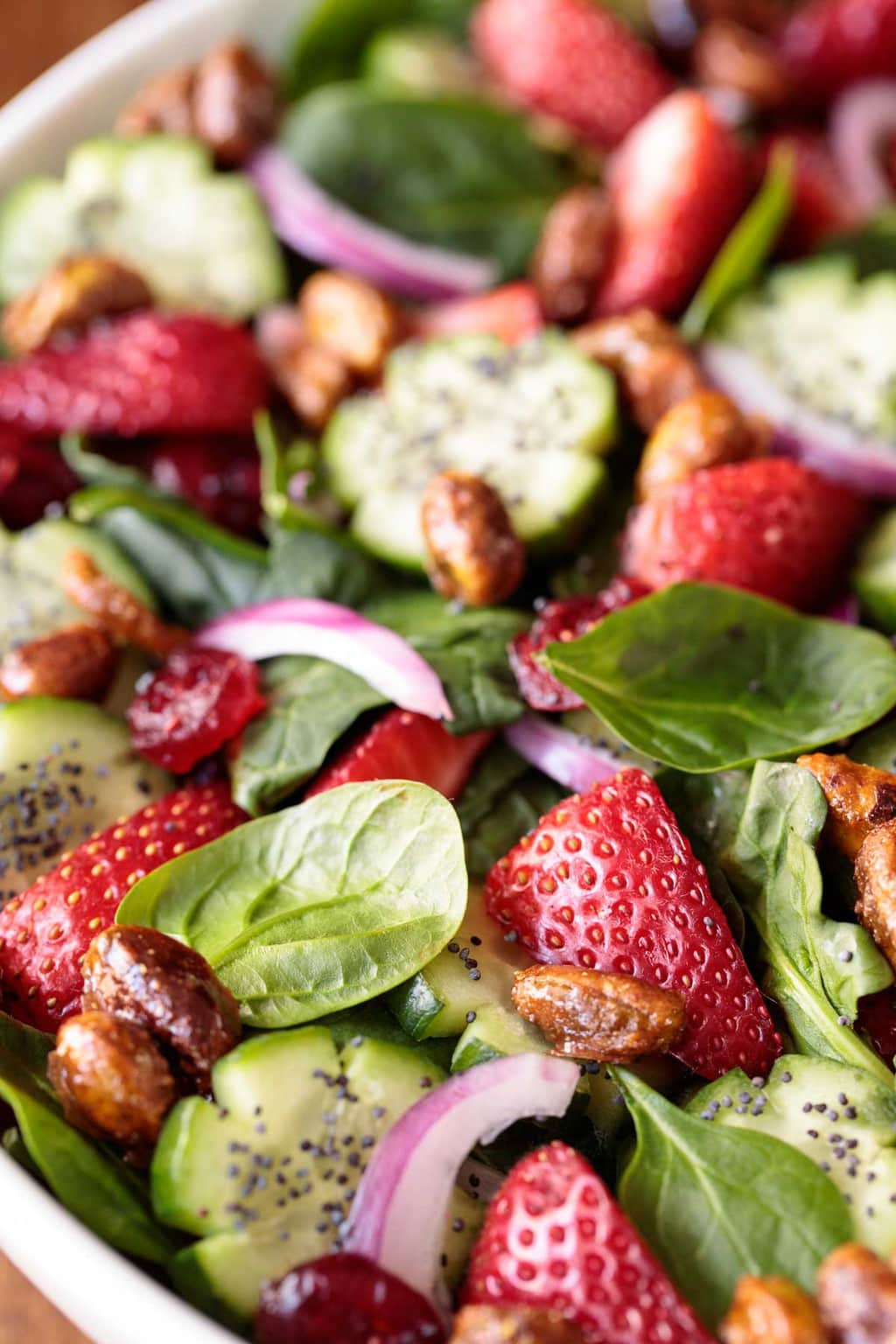 Closeup photo of a bowl filled with Strawberry Spinach Salad.