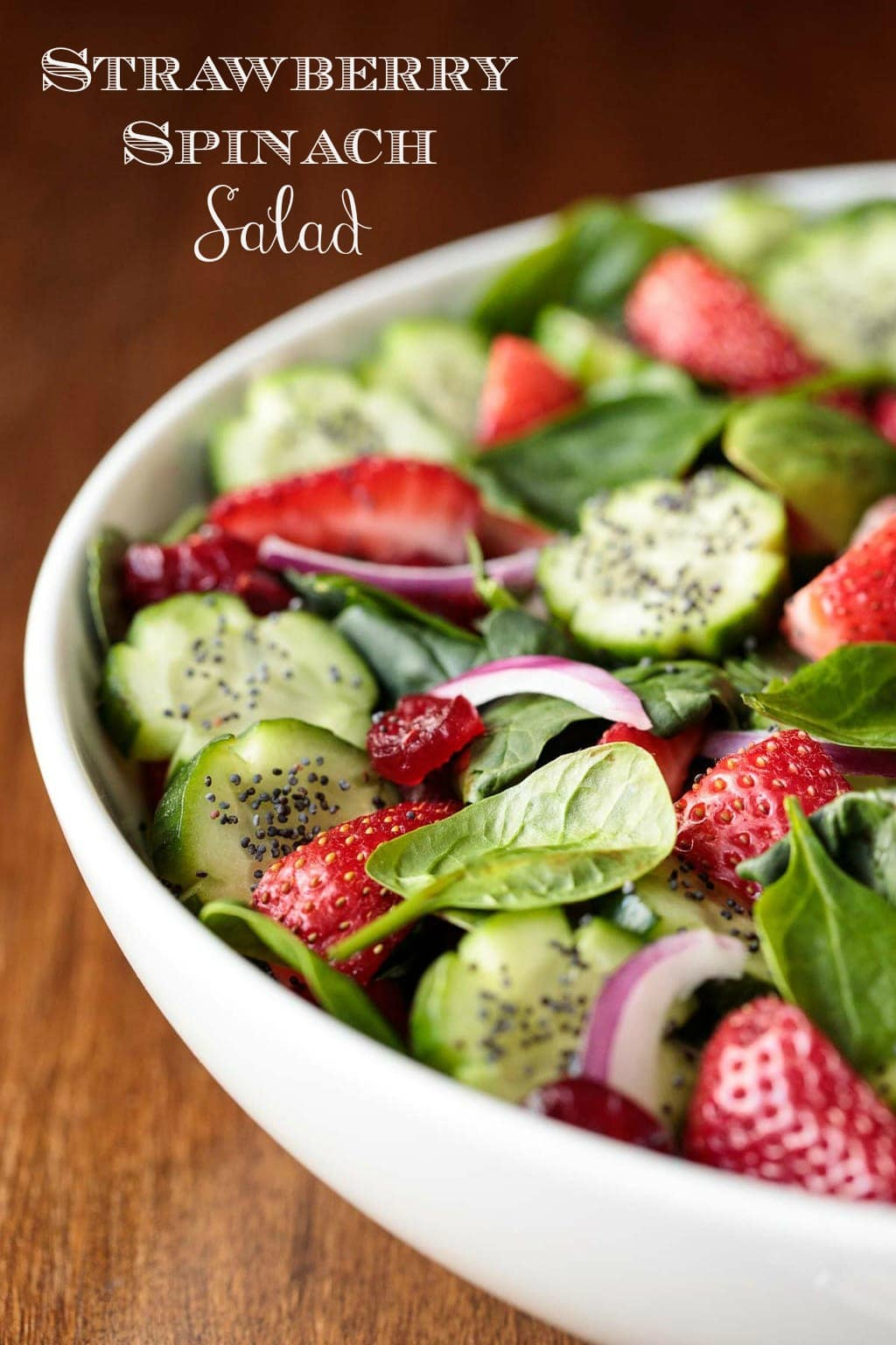This Strawberry Spinach Salad is pretty as a picture. The Basil Dressing and Sweet, Spicy Glazed Pistachios are the crowning glory! #spinachsalad #strwberryspinachsalad #basildressing #spinach #strawberries #cucumberflowers #cucumbers #springsalad