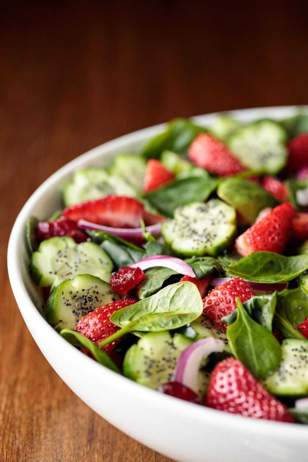 Photo of part of a Strawberry Spinach Salad in a white bowl on a wood table.