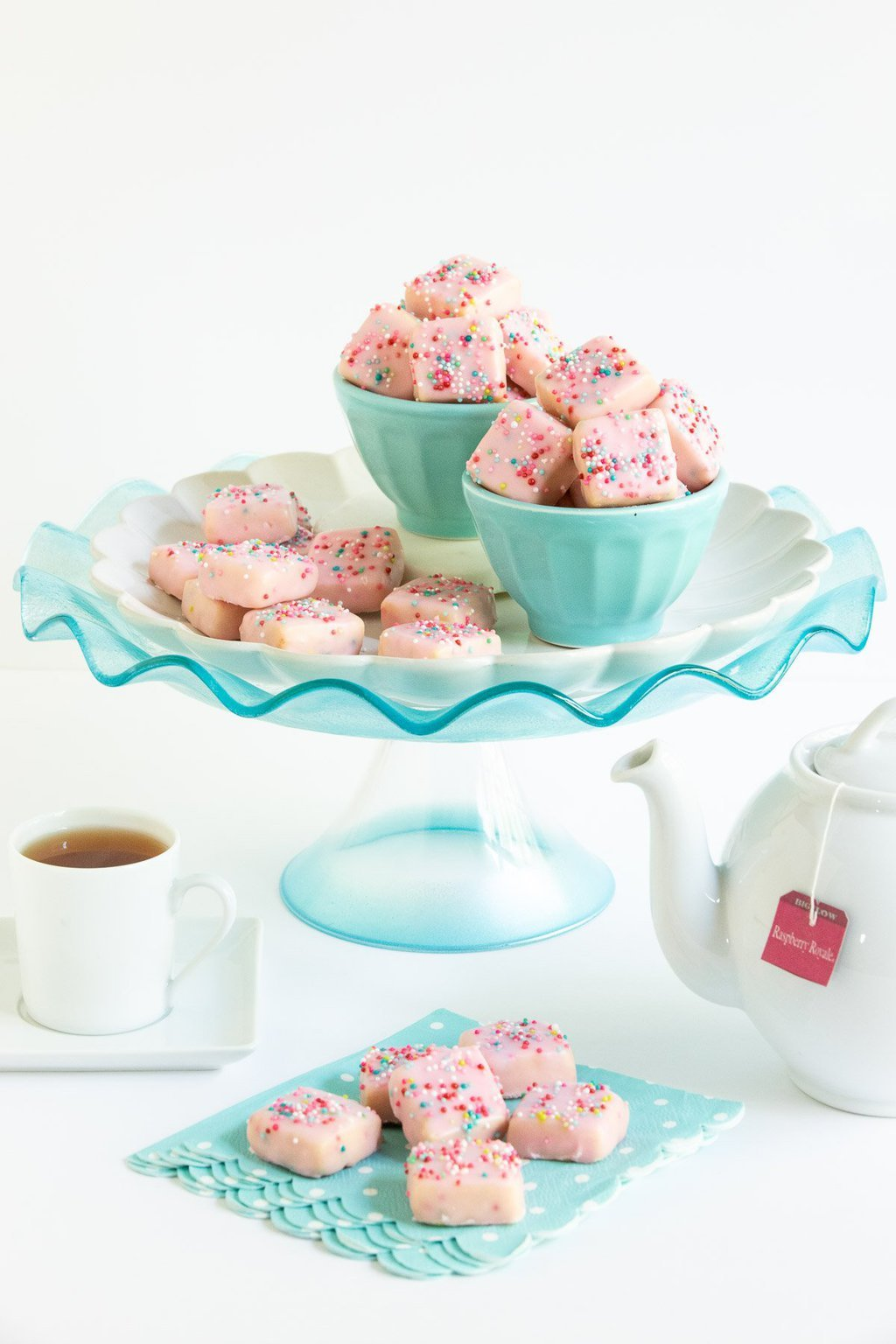 Vertical photo of Sugar Plum Fairy Shortbread Bites on a turquoise glass pedestal presentation plate with a cup of tea and a teapot in the foreground.