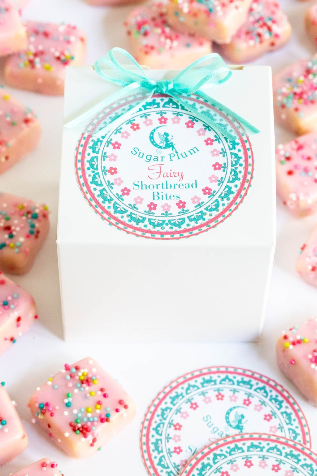 Vertical closeup photo of Sugar Plum Fairy Shortbread Bite custom gift labels and boxes.