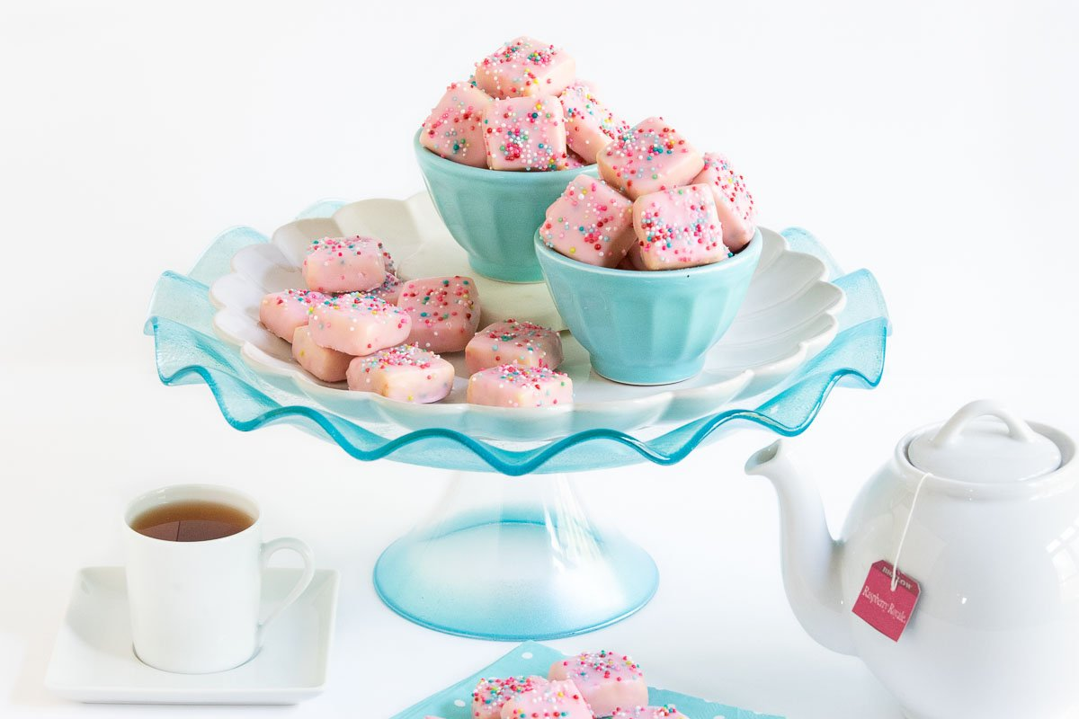 Horizontal photo of Sugar Plum Fairy Shortbread Bites on a turquoise glass pedestal platter surrounded by a cup of tea and a teapot.