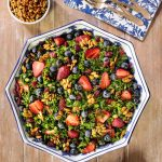 Overhead picture of summer kale salad on a wooden table with a blue and white napkin