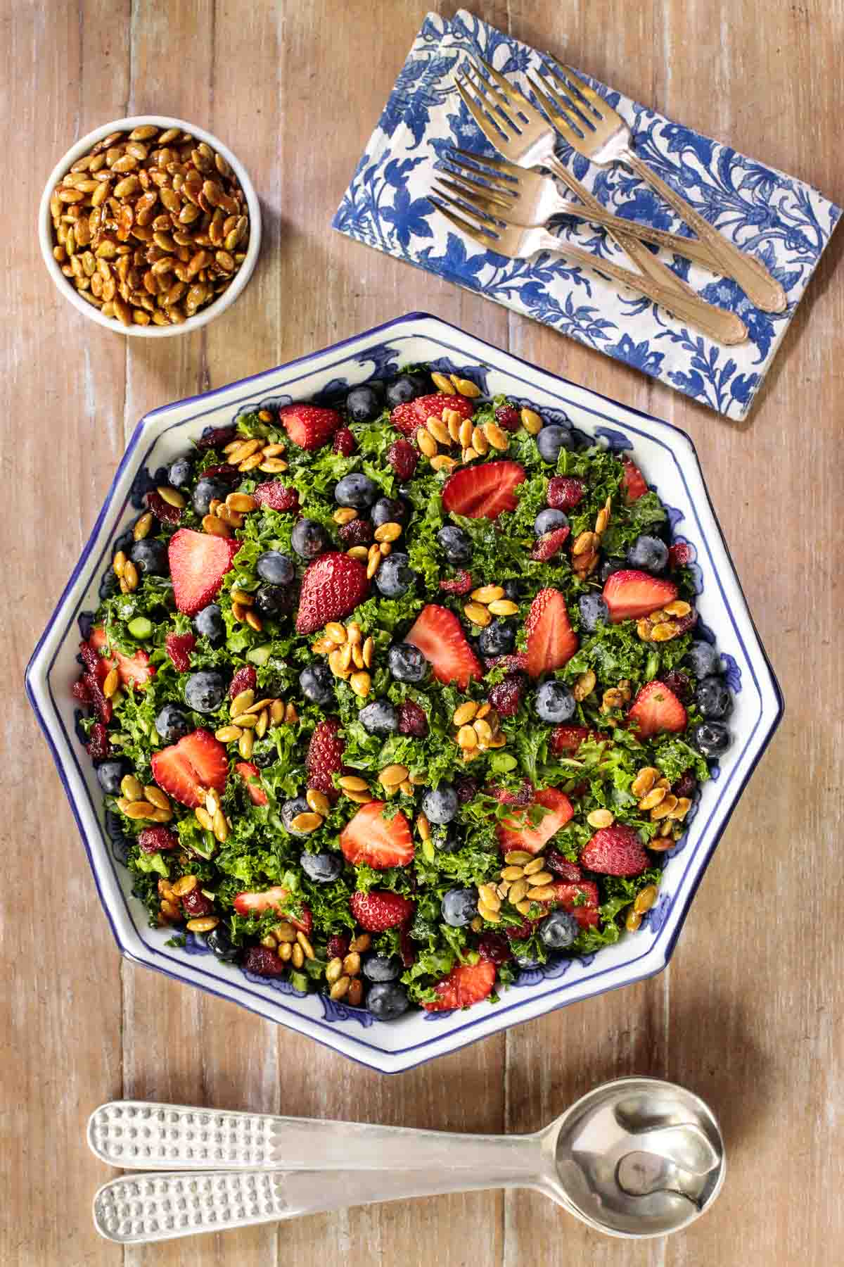 Overhead vertical photo of Strawberry Kale Salad on a wooden table with a blue and white patterned napkin.