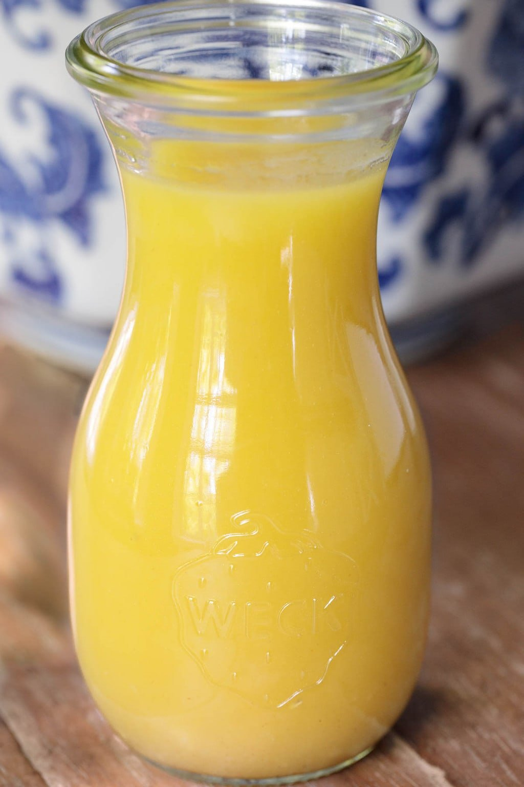 Closeup photo of a glass carafe of Honey Lemon dressing with a blue and white patterned serving bowl in the background.