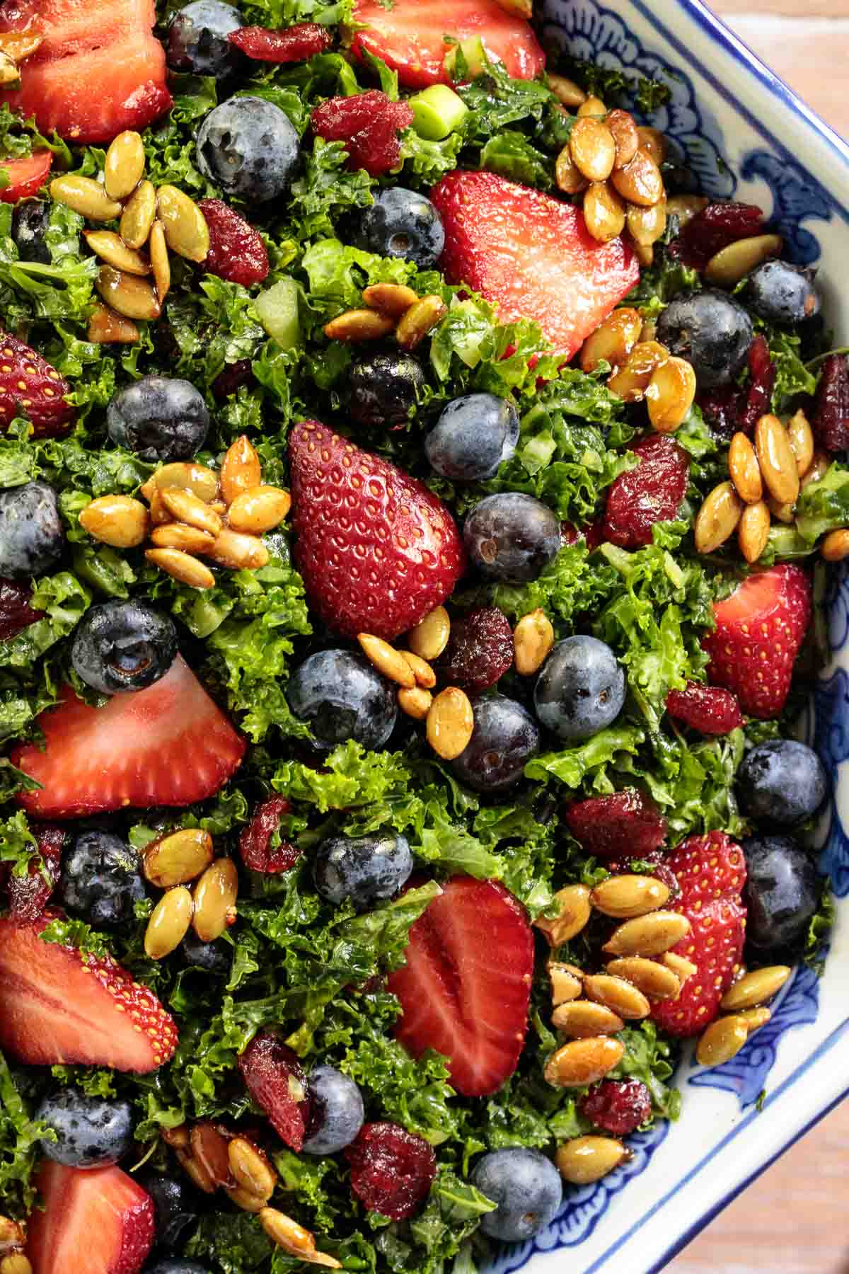 Overhead closeup photo of a salad bowl filled with Strawberry Kale Salad with Honey Lemon Dressing.
