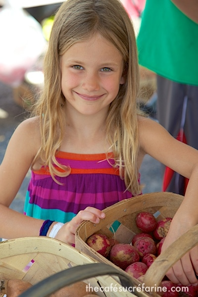 Annie helping to pick out vegetables for supper at a local farmer's market.