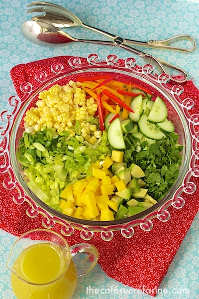 Overhead photo of a glass platter of Farmer's Market Salad with a pitcher of Sunny Honey Vinaigrette and salad tongs along side.